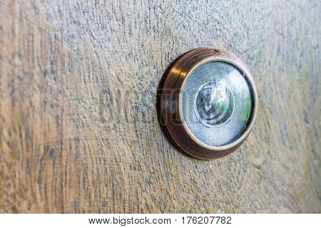 Abstract blur photo of old lens peephole on wooden door background for security in hotel.