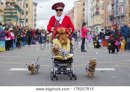 Badajoz Spain - February 28 2017: Elder woman with three dogs takes part at Carnival parade of troupes at Badajoz City. This is one of the best carnivals in Spain especially highlighting massive participation of people