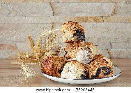 Sweet buns with poppy seeds on a white porcelain plate with a blue rim, on a wooden table and near a stone wall - sandstone. Poppy head and spikelets lie on sweet rolls