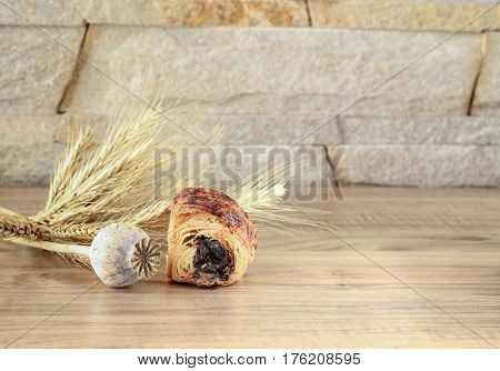 A sweet roll with poppy lies on a wooden table and near a stone wall - sandstone. Poppy head and spikelets lie near sweet roll