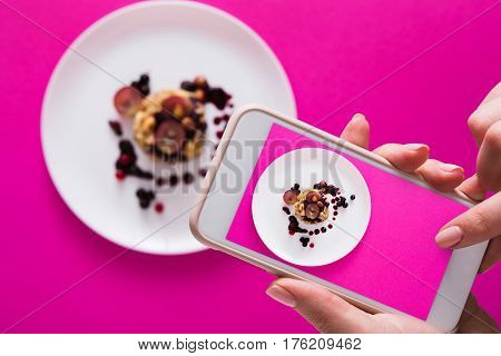 Top view close-up of female hands making flat lay food photo with phone for restaurant menu or social network. Oatmeal porridge on pink background, mockup, template, copy space, shallow depth of field