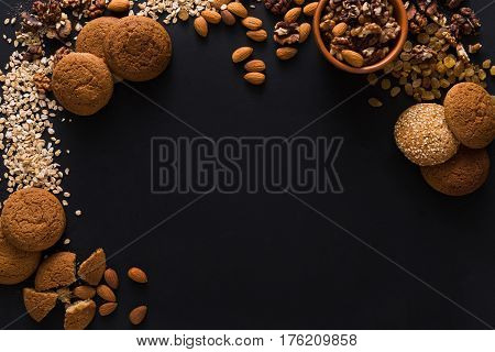 Healthy organic natural oat cookies made of wholegrain oat and nuts on dark table background, free copy space. Flat lay, top view, mockup, template, objects, nobody