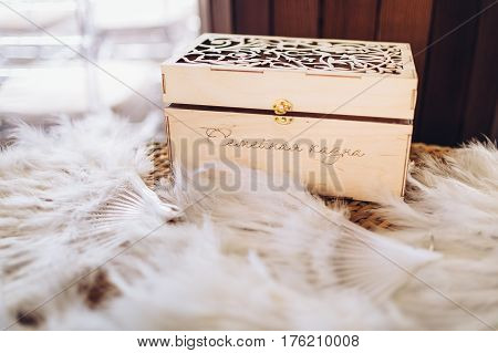 Vintage wooden box which is a family treasury on wedding, standing among white feathers