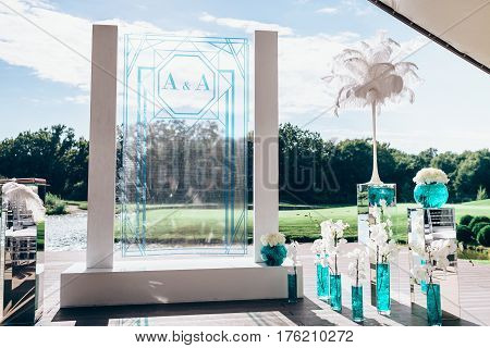 Wedding arch with bouquets of white peon and orchid flowers, in glass vases with blue liquid, and white big plume
