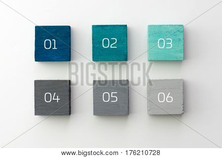 Index, menu or cover abstract back ground, consisting of six hand painted colored wooden cubes with numbers, on natural white background, with highlight on upper left. Blue, light blue to grey.