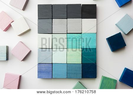 Selecting colors. Grey and light blue color sample cubes arranged on a natural white background, with pink and green cubes surrounding it.  flat lay or top view.