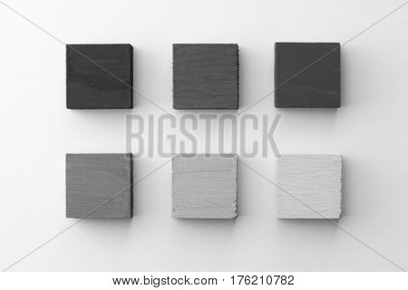 Index, menu or cover abstract back ground, consisting of six hand painted colored wooden cubes on natural white background, with highlight on upper left. Light to dark grey.