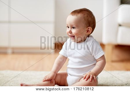 childhood, babyhood and people concept - happy little baby boy or girl sitting on floor at home