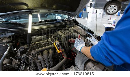 car service, repair, maintenance and people concept - auto mechanic man with digital multimeter testing battery at workshop