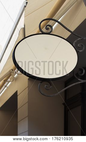 Vertical front view of empty round signage on a building with classical architecture