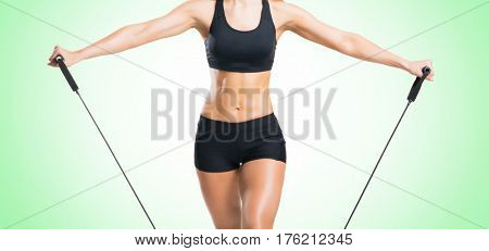 Fit, healthy and sporty woman in sportswear doing expander exercise green background.
