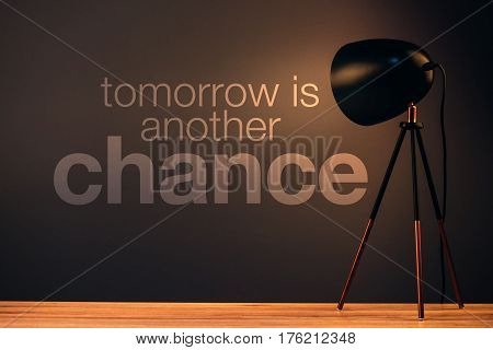 Tomorrow is another chance motivational quote on office wall illuminated by the desk lamp