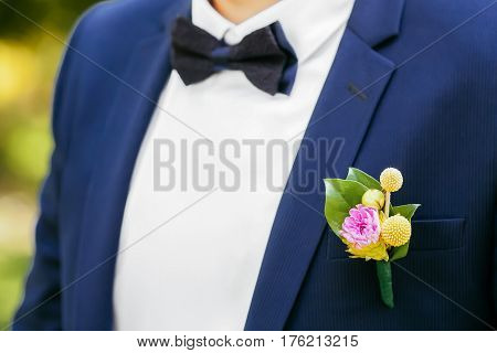 Pink peon boutonniere pinned to a grooms blue jacket