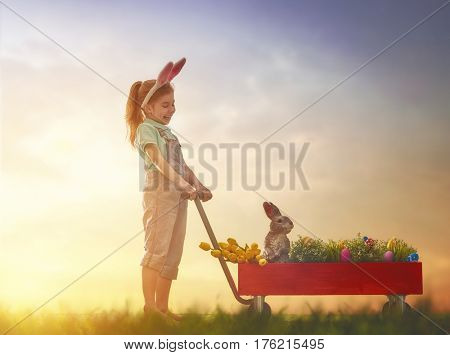 Cute little child wearing bunny ears. Girl has eggs, grass and rabbit. Kid on the lawn at Easter in the rays of the setting sun.