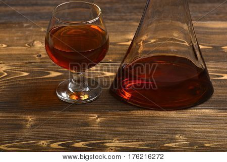 Glass And Carafe With Cognac, Whiskey On Wooden Table
