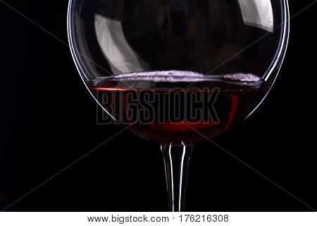 wineglass with wine isolated on black background side view closeup