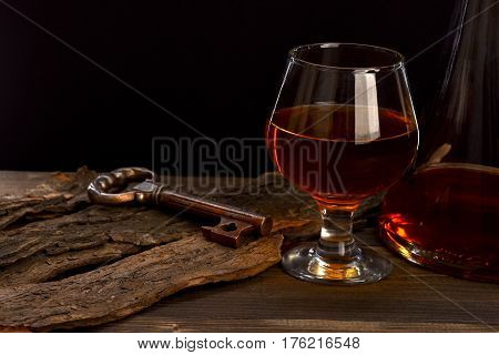 Glass, Carafe With Cognac, Whiskey And Key On Wooden Table