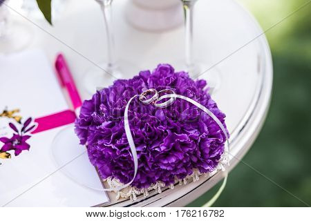 Wedding rings on purple support lying on small white table