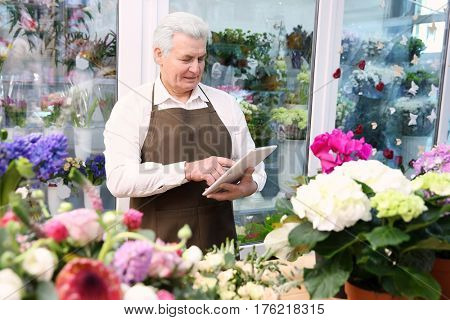 Male florist with tablet at flower shop