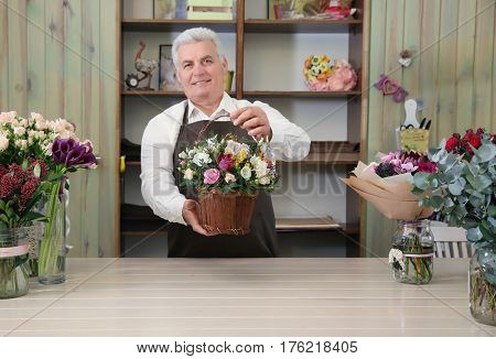 Male florist holding basket with flowers in flower shop
