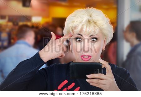 Blonde hair adult irritated woman with big eyes has video conversation by mobile phone