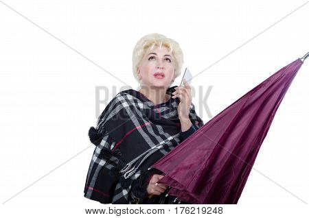 Blonde hair mature woman with closed violet umbrella looks up. Woman wearing plaid scarf calls by mobile phone. It seems she does not like rain. Horizontal portrait on white background