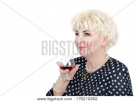 Blonde hair adult woman in pearl necklace holds glass of brandy posing on  white background. Side mid-shot