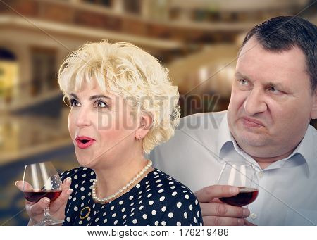Middle-aged lady with admiration facial expression and chubby face displeased mature man look at one way. Each holds glass of brandy by hand. Side medium close up shot on blurred indoors background