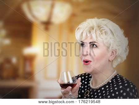 Lovely surprised adult woman holds glass of brandy. Blonde hair lady looks upward with open mouth. She wears polka dot suit pearl necklace and bracelet. Blurred interior background