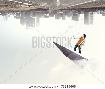 Hipster guy surfing sky . Mixed media
