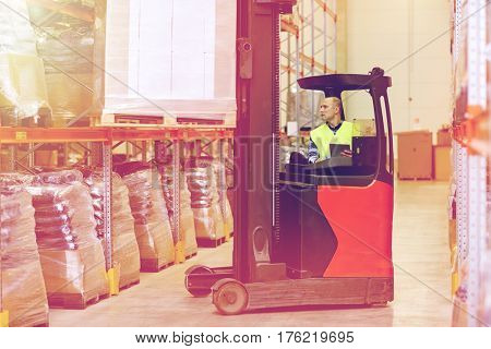wholesale, logistic, loading, shipment and people concept - man or loader with tablet pc computer and forklift or loader loading boxes at warehouse