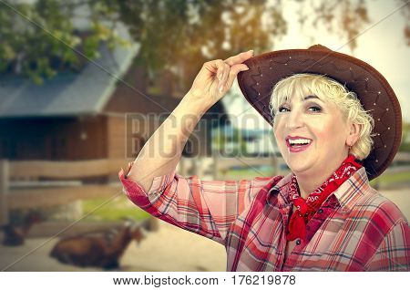 Happy cowgirl tips her brown hat and shines posing on ranch background out of focus. Mature woman wears red plaid shirt and neck scarf. Bright sunny day. Horizontal side medium close up shot