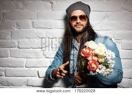Portrait photo of rocker guy in sunglasses and woolly hat standing against brick wall holding bouquet of flowers for mother's day.