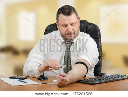 Mature businessman administers medication into his vein at workplace