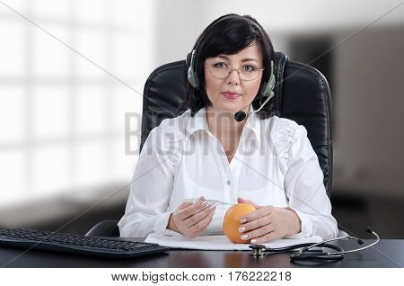 Telecare doctor in headset explains with grapefruit how to give a subcutaneous injection