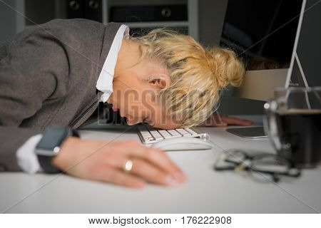 Woman sleeping on computers keyboard at the office