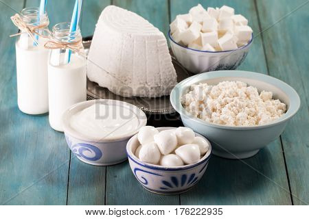 Tasty Healthy Dairy Products On A Table On A Blue Background: Sour Cream, Cottage Cheese, Mozzarella