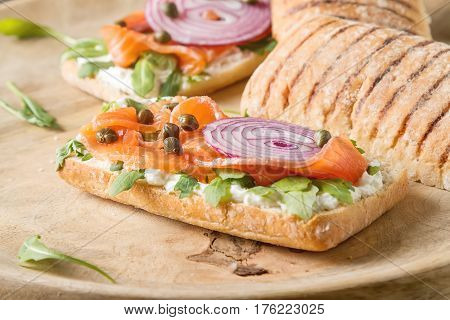 Homemade Baguette With Smoked Salmon, Onions And Arugula. Wooden