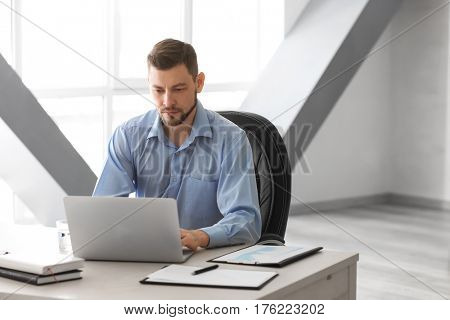 Handsome manager working with laptop in office