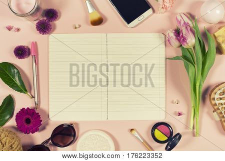 Creative beauty feminine arrangement of flowers and cosmetics. Flat lay. Pink background. Top view