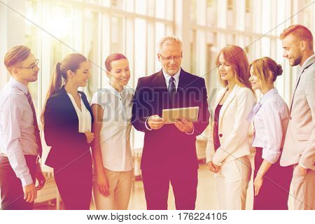people, technology, work and corporate concept - business team with tablet pc computer at office
