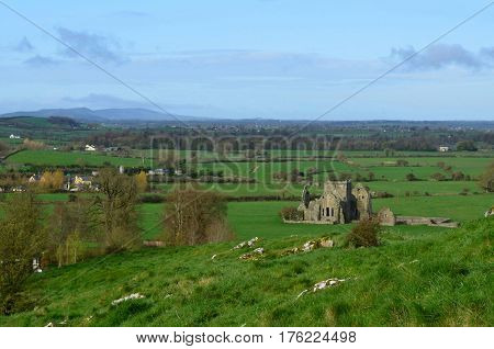 Lush green field with the ruins of Hore Abbey in the distance.