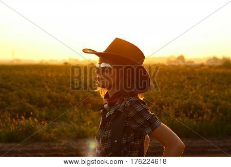 A silhouette of a cowgirl with a beautiful sunset in the background.
