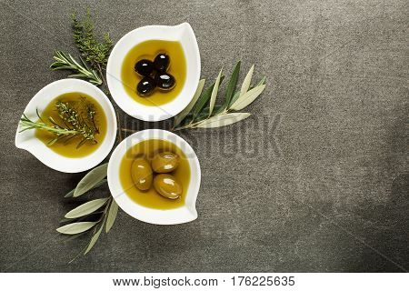 Olive oil with fresh herbs on stone background