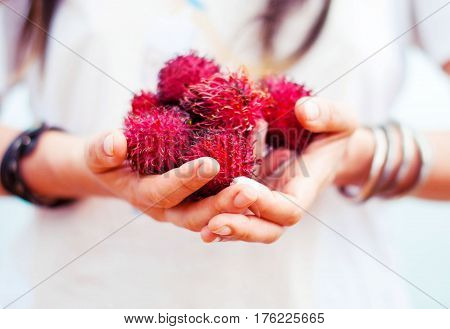 A girl with bracelets is holding a Litchi fruit