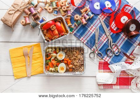 Desktop with lunch box healthy food delivery for dressmaker. Flat lay shot of foil container with diet meal for fashion designer at workplace. Healthy nutrition with fruits, vegetables and proteins