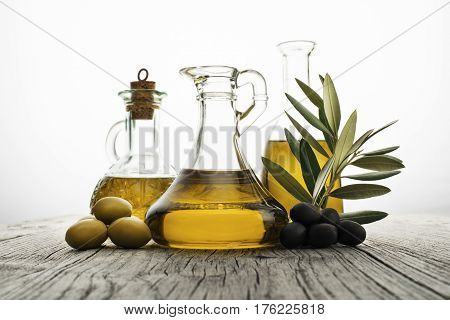 Olive oil with branch on the wooden background
