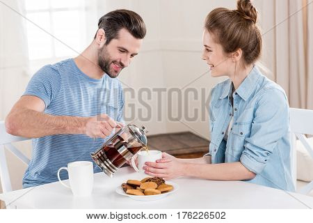 Smiling young couple drinking tea with cookies at home