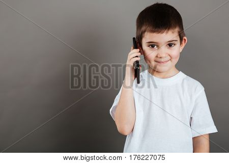 Happy little boy standing and talking on mobile phone over grey background