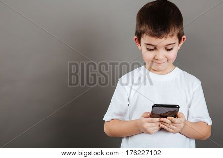 Cute little boy holding and using mobile phone over grey background